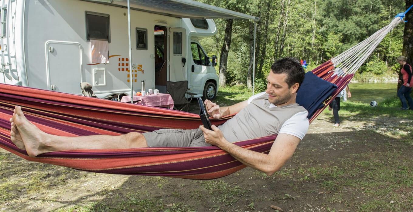 Man laying in hammock at a campsite looking at tablet